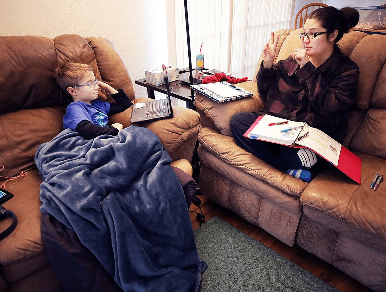 Lex Reynolds, 9, does classroom remote learning with his mom Athena in the living room of their Sierra Vista home last week.