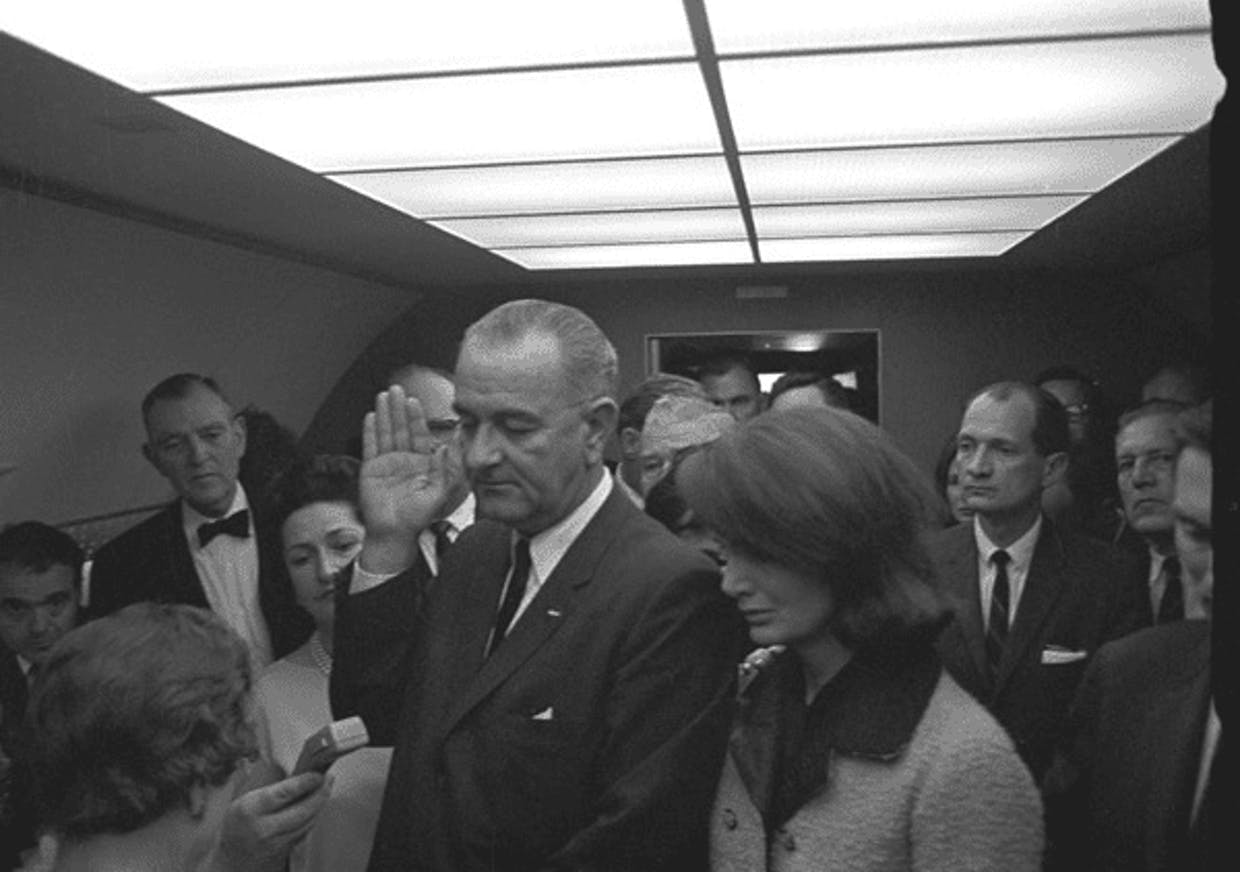 Johnson, swearing in on Air Force One, parked at Dallas Love Field. Jacqueline Kennedy stands to his left.