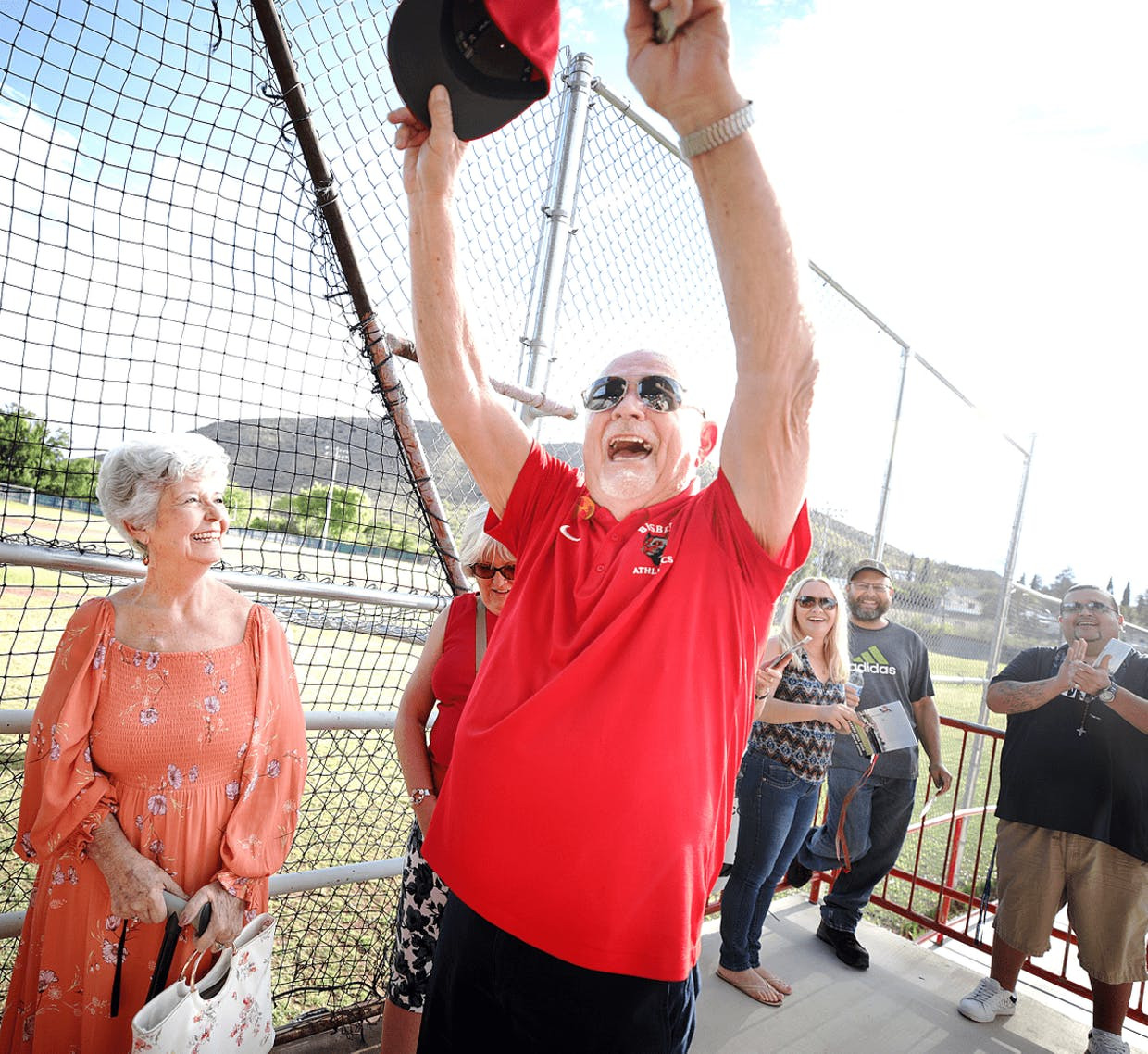Bisbee baseball legend Mike Frosco sends a cheer right back to friends, family, former teammates and players in the Warren Ballpark stands as they applaud his appearance during Saturday's dedication naming the field after him. Frosco's wife Sharon is at his side.