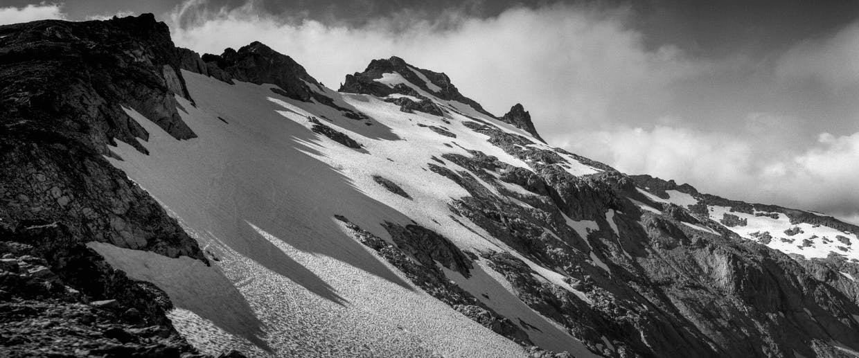 A ridgeline on Mt. Daniel casts a shadow over snowfields hugging the mountain, July 21. Scramblers commonly take a ridgetop route from left to right in order to reach the top.